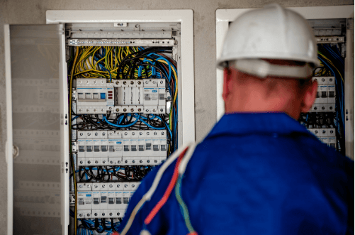 Eletricista de costas checando painel