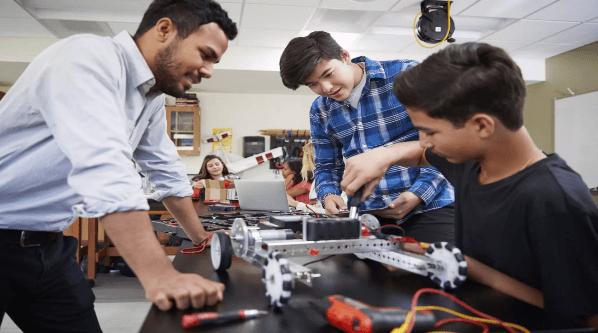 Aluno de robotica montando robo na sala de aula