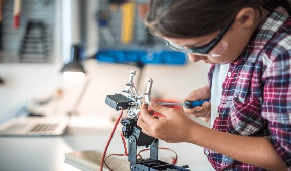 Crianca apertando parafusos de um braco robotico