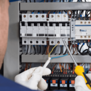 Eletricista de comandos elétricos apertando um parafuso no painel elétrico industrial