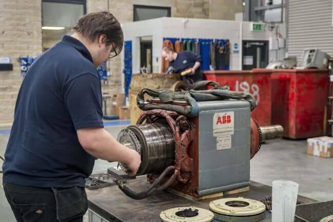 Homem mexendo em um motor industrial no chão de fábrica