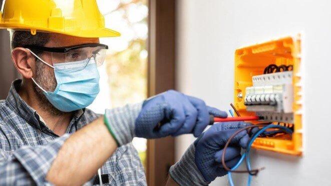 Eletricista que está fazendo a manutenção dos comandos elétricos através do painel qdc residencial