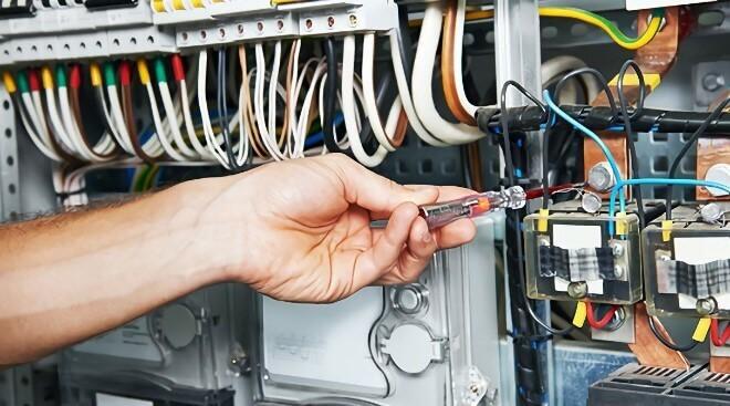 Homem que está verificando se há defeitos no circuito de comandos em uma indústria através de uma chave