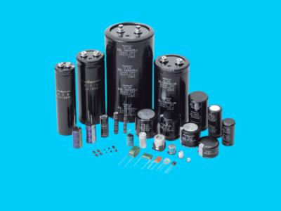Diversos modelos de capacitores grandes e pequenos na frente de um fundo azul