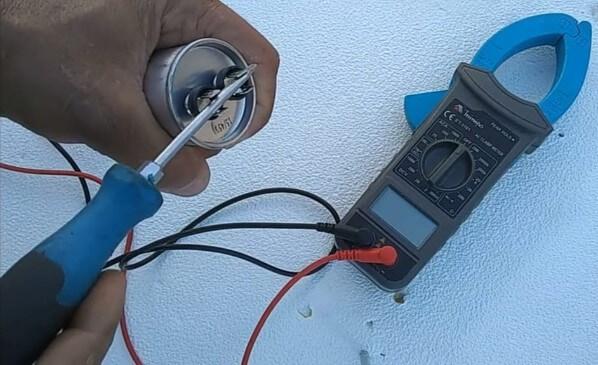 Pessoa segurando uma chave de fenda e dando curto no capacitor para descarregar o componente por completo