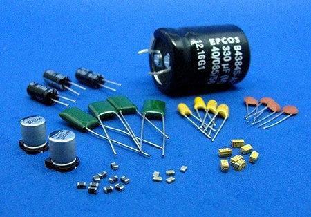 Diversos capacitores que estão em cima de uma mesa azul