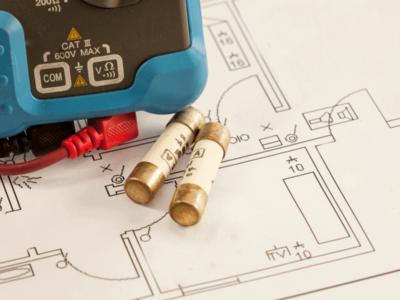 Multímetro e fusível em cima de um diagrama unifilar elétrico de uma casa