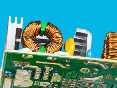 Indutores e dissipadores de calor soldados em uma placa de circuito vistos debaixo