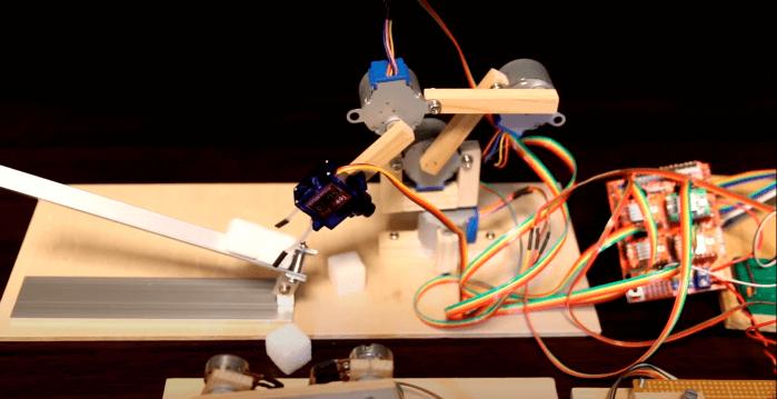Imagem de um braço robótico industrial feito de palitos de madeira, motor de passo e Arduino