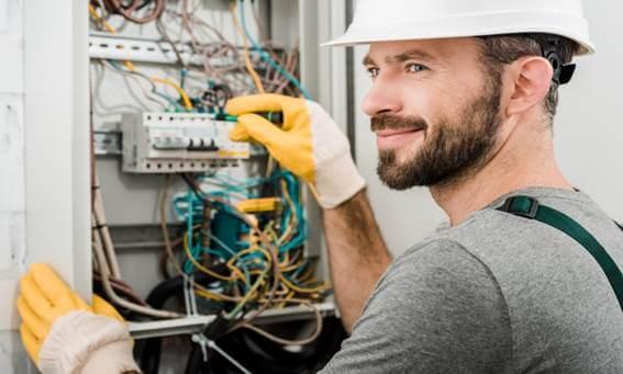 Homem eletricista mexendo em uma instalação elétrica e olhando para o lado