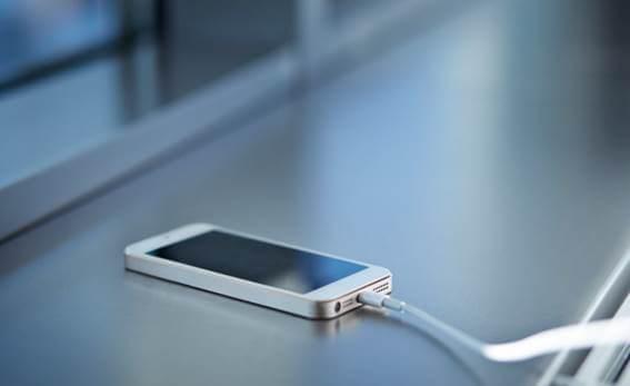 Telefone em cima de uma mesa sendo carregado através de um cabo branco