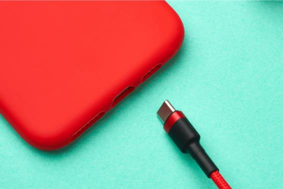 Smartphone vermelho e cabo em trança têxtil em um fundo verde