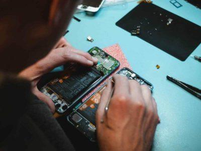 Tecnico em manutencao de celulares fazendo o conserto de um smartphone em sua bancada