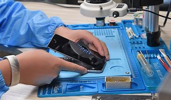 Bancada azul que está servindo para uma mulher fazer a recuperação de um telefone defeituoso