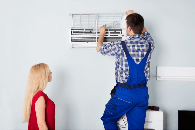 Mulher de rosa observando o técnico de macacao azul realizar a instalação de um ar condicionado em sua casa