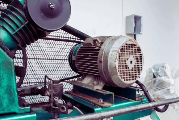 Motor trifásico de uma máquina velha que está ligado a ela através de uma correia