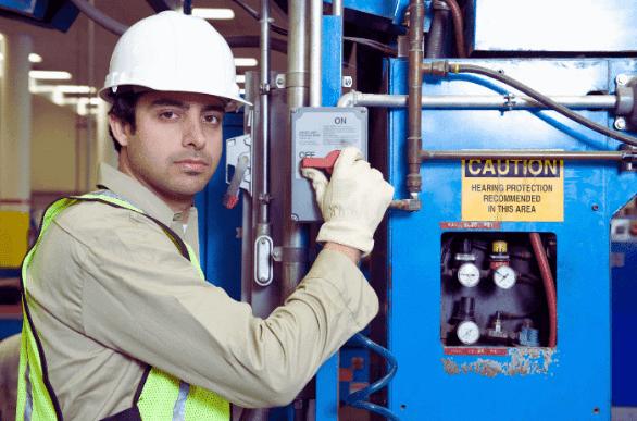 Técnico eletricista no chão de fábrica com o devido EPI executando uma partida direta através de um painel azul