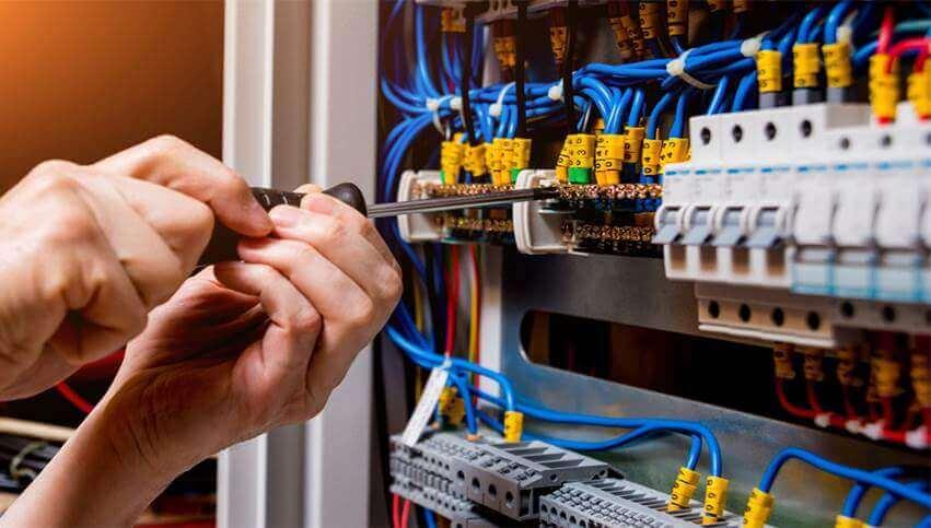 Eletricista apertando os parafusos de um painel QDC que possui diversos fios azuis de um projeto eletrico residencial