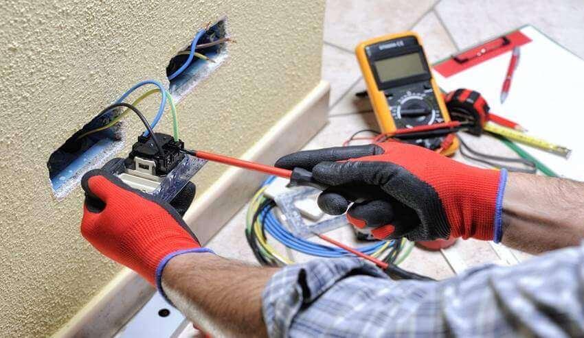 Profissional da eletrica com luvas e fazendo a instalacao de uma tomada na parede