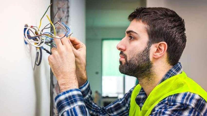 Eletricista organizando ummonte de fios que estao saindo de uma parede branca simbolizando uma instalacao de um projeto elétrico